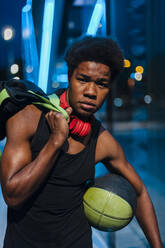 Portrait of a confident young man with headphones and basketball in the city at night - JMPF00049