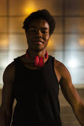 Portrait of a confident young man with headphones at night with city lights - JMPF00052