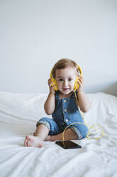 Baby girl at home listening to music on bed - EBBF00324