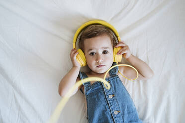 Baby girl at home listening to music on bed - EBBF00327