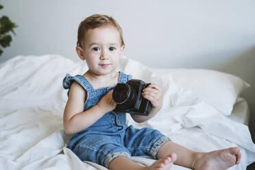 Baby girl holding camera at home - EBBF00348