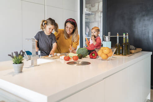 Baby daughter sitting on island while mother and girl preparing food in kitchen - JAF00018