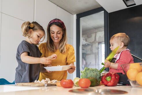 Mother and girl preparing food while baby daughter sitting on kitchen island - JAF00024