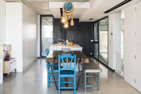 Illuminated lights hanging over dining table in modern kitchen at home - JAF00033