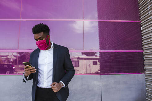 Businessman wearing mask using smart phone while standing against pink glass wall - LJF01635