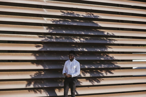 Smiling businessman standing against modern built structure with shadow of tree - LJF01674