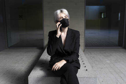 Female professional wearing mask talking over smart phone while sitting in office - TCEF00830