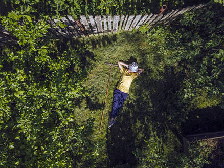 Aerial view of mid adult woman resting on grassy land in garden - KNTF04746