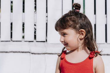Portrait of little girl wearing red summer dress in front of white wall - GEMF03904