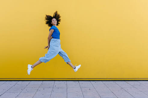 Pretty woman jumping for joy in front of yellow wall - TCEF00841