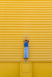 Smiling woman reaching up at yellow wall, standing on platform - TCEF00850