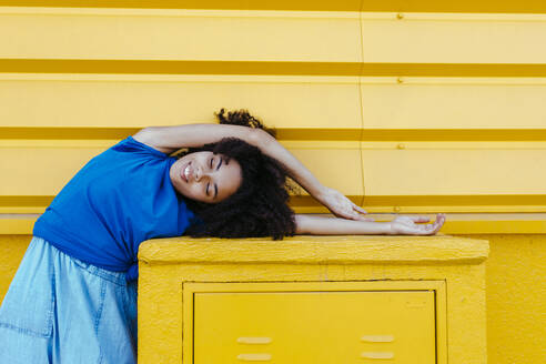 Dreamy woman bending sideways over platfrom in front of yellow wall - TCEF00853