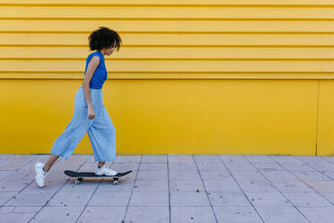 Young woman skateboarding in front of yellow wall - TCEF00856