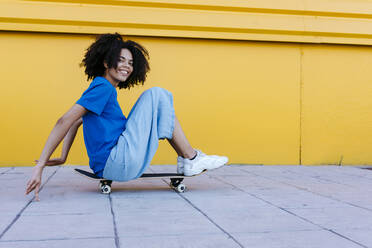 Smiling young woman sitting on skateboard in front of yellow wall - TCEF00859