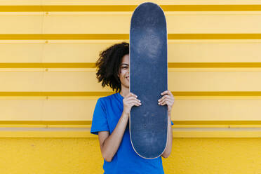 Young woman holding skateboard in front of face, looking at camera - TCEF00865