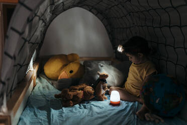 Three year old girl playing scouts in her bed with a world ball and stuffed animals - GEMF03906