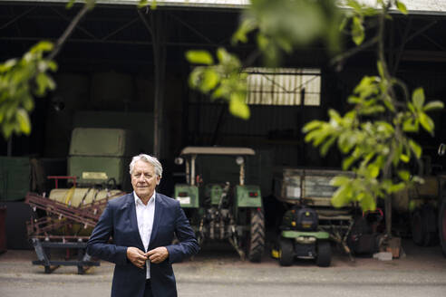 Senior businessman on a farm with tractor in barn - GUSF04025