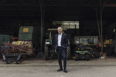 Senior businessman standing on a farm with tractor in barn - GUSF04034