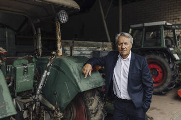 Portrait of a senior businessman on a farm with tractor in barn - GUSF04037