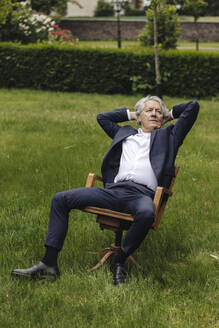 Relaxed senior businessman sitting on a chair in a rural garden looking up - GUSF04046