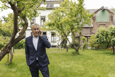 Senior businessman on the phone in a rural garden - GUSF04052