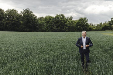 Senior businessman on a field in the countryside - GUSF04058
