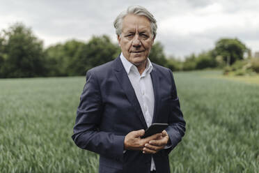 Portrait of senior businessman holding smartphone on a field in the countryside - GUSF04064