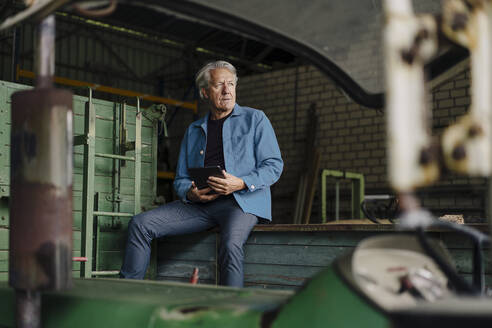 Senior man with tablet sitting on a trailer in barn - GUSF04121