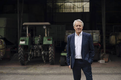 Portrait of senior businessman holding laptop on a farm with tractor in barn - GUSF04142