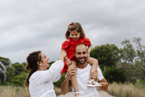 Cheerful family enjoying at countryside against cloudy sky - EGAF00358