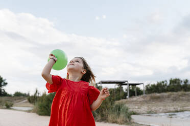 Cute girl playing with balloon at beach against cloudy sky - EGAF00376