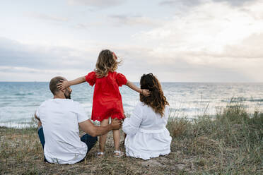Family spending quality time at beach against cloudy sky - EGAF00382