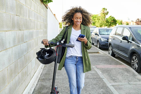 Happy young woman using smart phone while walking with electric push scooter on sidewalk - KIJF03157