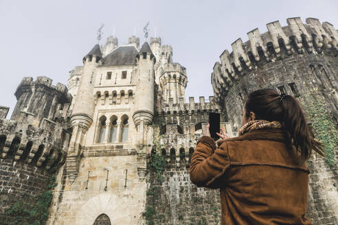 Woman photographing Butron Castle with smart phone, Basque Country, Spain - XLGF00294