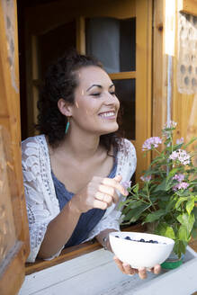 Happy woman holding blueberries in bowl while peeking through window of cottage - LVVF00135