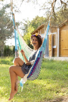 Cheerful young woman wearing wreath while sitting in hammock at yard - LVVF00138