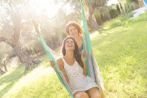 Happy young woman pushing friend on hammocks at yard during sunny day - LVVF00144