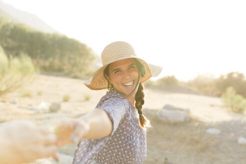 Cheerful young woman wearing sun hat during sunny day - LVVF00156