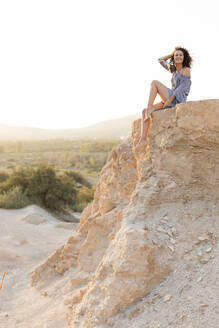 Happy young woman sitting on cliff at countryside against clear sky - LVVF00165