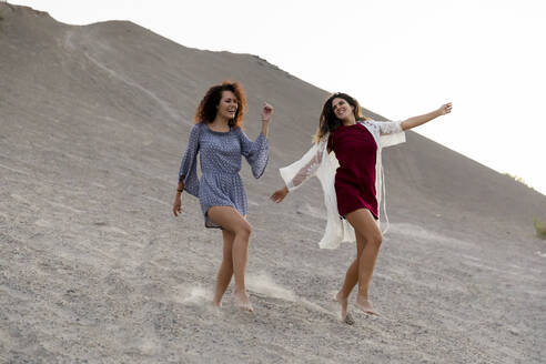 Cheerful female friends dancing on hill at countryside - LVVF00177