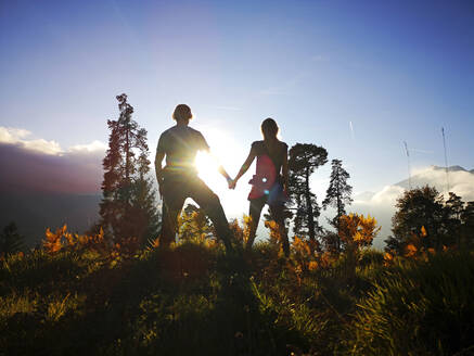 Germany, Bavaria, Garmisch-Partenkirchen, Silhouettes of man and woman holding hands on landscape at sunset - ECPF00974