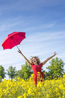 Carefree woman with arms raised holding umbrella while standing amidst oilseed rapes - BFRF02257