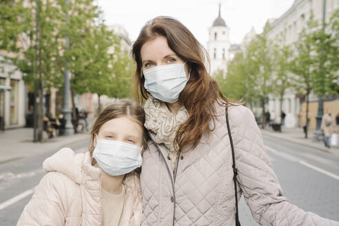 Mother and daughter wearing masks standing on street in city - AHSF02796