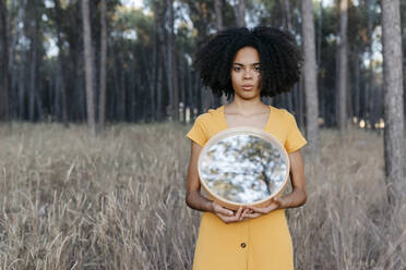 Young woman with afro hair holding mirror while standing on land in forest - TCEF00874