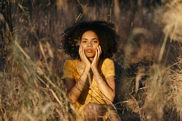 Young woman with afro hair sitting amidst plants in forest during sunset - TCEF00877