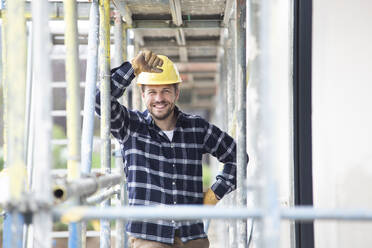 Smiling construction worker wearing helmet standing by scaffold at construction site - MJFKF00402
