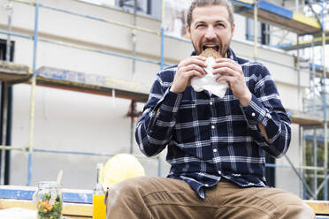 Construction worker eating bread while sitting against building at construction site - MJFKF00408