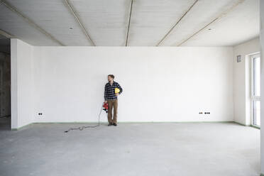 Construction worker holding work tool and helmet while standing in empty house - MJFKF00414