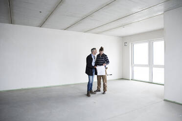 Architect and construction worker discussing blueprint while standing in empty house - MJFKF00417