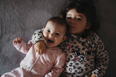 Girl touching baby sister's cheeks while lying on bed at hone - GEMF03919